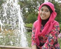 Musulmanes femeninos que se sientan cerca de la fuente fotos de archivo
