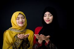 musulmanes jovenes religiosos dos mujeres que ruegan sobre fondo negro Foto de archivo