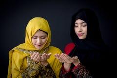 musulmanes jovenes religiosos dos mujeres que ruegan sobre fondo negro Fotografía de archivo
