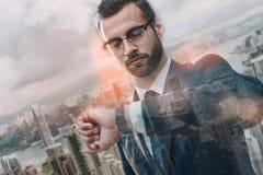 Muszę być tam w czasie Ufny biznesmen patrzeje jego zegarek w kostiumu podczas gdy stojący outdoors z nowożytnym biurem obraz stock