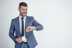 Musz? by? tam? w czasie Uśmiechnięty biznesmen patrzeje na jego chwytach i wristwatch jego coffe odizolowywał na białym tle zdjęcia royalty free