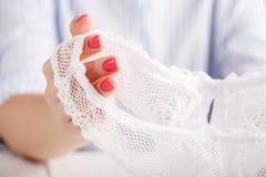 Mutandine trasparenti sexy su fondo bianco in mani femminili immagine stock