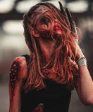 Mutant girl portrait in wounds and ulcers with nails in her head. And claws instead of fingers. On her head and hands is bandage stock photography