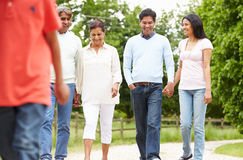 Muti-Generation Indian Family Walking In Countryside. Holding Hands Whilst Talking To Each Other Royalty Free Stock Photos