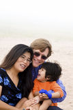 Mutiracial family sitting on beach Stock Photos