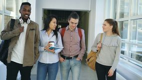 Mutli-ethnic group of male and female students are walking in big corridor of university discussing study smiling and