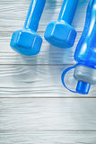 Muto-campane blu della bottiglia di acqua sul concetto di legno di forma fisica del bordo Immagini Stock