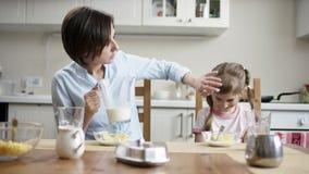 Mutter addieren Milch, um zu rollen voll von den Corn-Flakes für ihre Tochter, aber sie lehnt ab stock footage