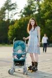 Mutter auf Rollschuhen mit Kinderwagen Stockfoto