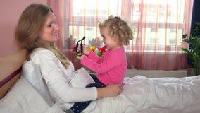 Mutter-Augengläser des netten Tochtermädchens versuchende, die auf Bett sitzen Glückliche Familienmädchen stock video footage