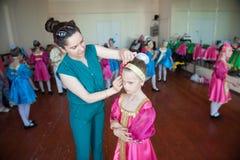 Mutter bereitet ihre unglückliche Tochter für ein Konzert an der Tanzschule vor stockfoto