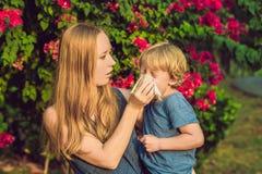 Mutter betrachtet seinen Sohn, der zum Blütenstaub allergisch ist stockfoto