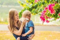 Mutter betrachtet seinen Sohn, der zum Blütenstaub allergisch ist stockbild