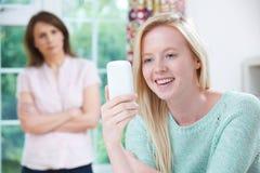 Mutter betroffen über den Gebrauch der jugendlich Tochter von Handy stockbild