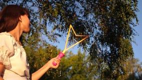 Mutter bl?st gro?e Seifenblasen im Park im Sommer, im Fr?hjahr f?r Kinder auf Dekorationen f?r den Feiertag stock footage
