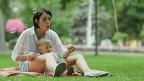Mutter brennt die Blasen durch, die auf Plaid mit kleinem Sohn im Park sitzen stock video