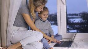 Mutter bringt ihrer Tochter bei, wie man Laptop benutzt stock video