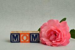 Mutter buchstabierte mit bunten Alphabetblöcken und ein rosa stieg Lizenzfreies Stockbild