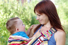 Mutter carrys Sohn im Babyriemen Stockbild