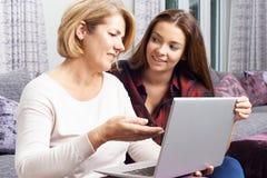 Mutter der jugendlichen Tochter, zeigend, wie man Laptop-Computer benutzt Lizenzfreie Stockfotografie