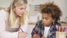 Mutter der jungen Frau, die ihrem Sohn hilft, Schulhausarbeit vorzubereiten stock footage