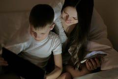 Mutter der jungen Frau und ihr aufpassender interessanter Film des Sohns zusammen auf Tablette und Lachen unter der Decke Mutter  Lizenzfreie Stockbilder
