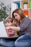 Mutter, die auf den Computer mit Sohn zeigt Stockbild