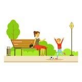 Mutter, die auf der Bank Wathing ihren Sohn spielt Fußball, Teil Leute in der Park-Tätigkeits-Reihe sitzt Stockbild