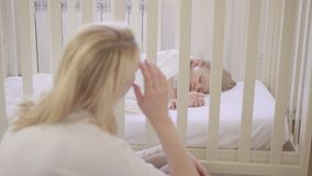 Mutter, die auf schlafendem Kind im Feldbett schaut stock footage