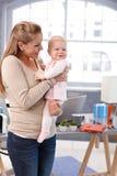 Mutter, die Baby beim Armlächeln hält Stockfotografie