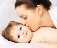 Mutter, die Baby im Bett küsst Lizenzfreie Stockfotos