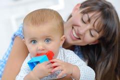 Mutter, die am Baby kaut Spielzeug lächelt lizenzfreies stockbild