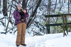Mutter, die Baby während des Wegs im Schnee hält lizenzfreie stockfotografie