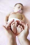 Mutter, die Babyfüße vetical hält Lizenzfreie Stockfotos