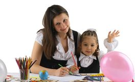 Mutter, die bei der Heimarbeit zu ihrer Tochter hilft lizenzfreies stockbild