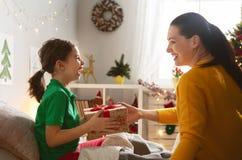 Mutter, die Cristmas-Geschenk zur Tochter vorbereitet lizenzfreies stockbild