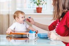 Mutter, die das Baby heraus hält ihre Hand mit einem Löffel des Breis in der Küche einzieht Gefühle eines Kindes beim Essen stockfotos