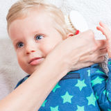 Mutter, die das Kleinkind kämmt Lizenzfreie Stockfotografie