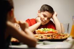 Mutter, die dem überladenen Sohn Salat anstelle der Pizza gibt stockfotografie