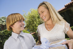 Mutter, die dem Sohn Geschenk gibt stockbild