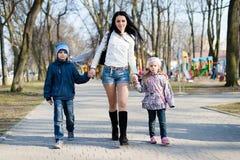 Mutter, die in den Park mit ihrem glückliche lächelnder des Sohns und der Tochter u. schauender Kamera auf Frühling oder Herbst g Stockbilder