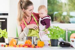 Mutter, die in der Küche beim Tragen des Kindes arbeitet Stockbilder