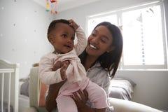 Mutter, die in der Kindertagesstätte mit Baby-Tochter sitzt Lizenzfreie Stockbilder