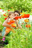 Mutter, die der Tochter Blumen zeigt Lizenzfreies Stockbild