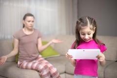 Mutter, die die ihre Tochter spielt Videospiele frustriert lizenzfreies stockbild