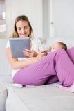 Mutter, die digitale Tablette bei der Fütterung ihres Babys mit Milchflasche verwendet Lizenzfreie Stockfotos