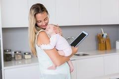 Mutter, die digitale Tablette beim Tragen ihres Babys in der Küche verwendet Lizenzfreies Stockfoto