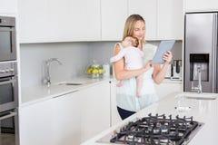 Mutter, die digitale Tablette beim Tragen ihres Babys in der Küche verwendet Stockbild
