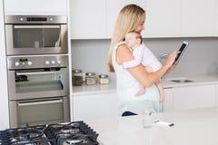 Mutter, die digitale Tablette beim Tragen ihres Babys in der Küche verwendet Lizenzfreies Stockbild