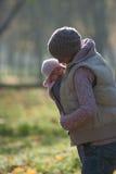 Mutter, die draußen Baby umarmt Lizenzfreie Stockbilder